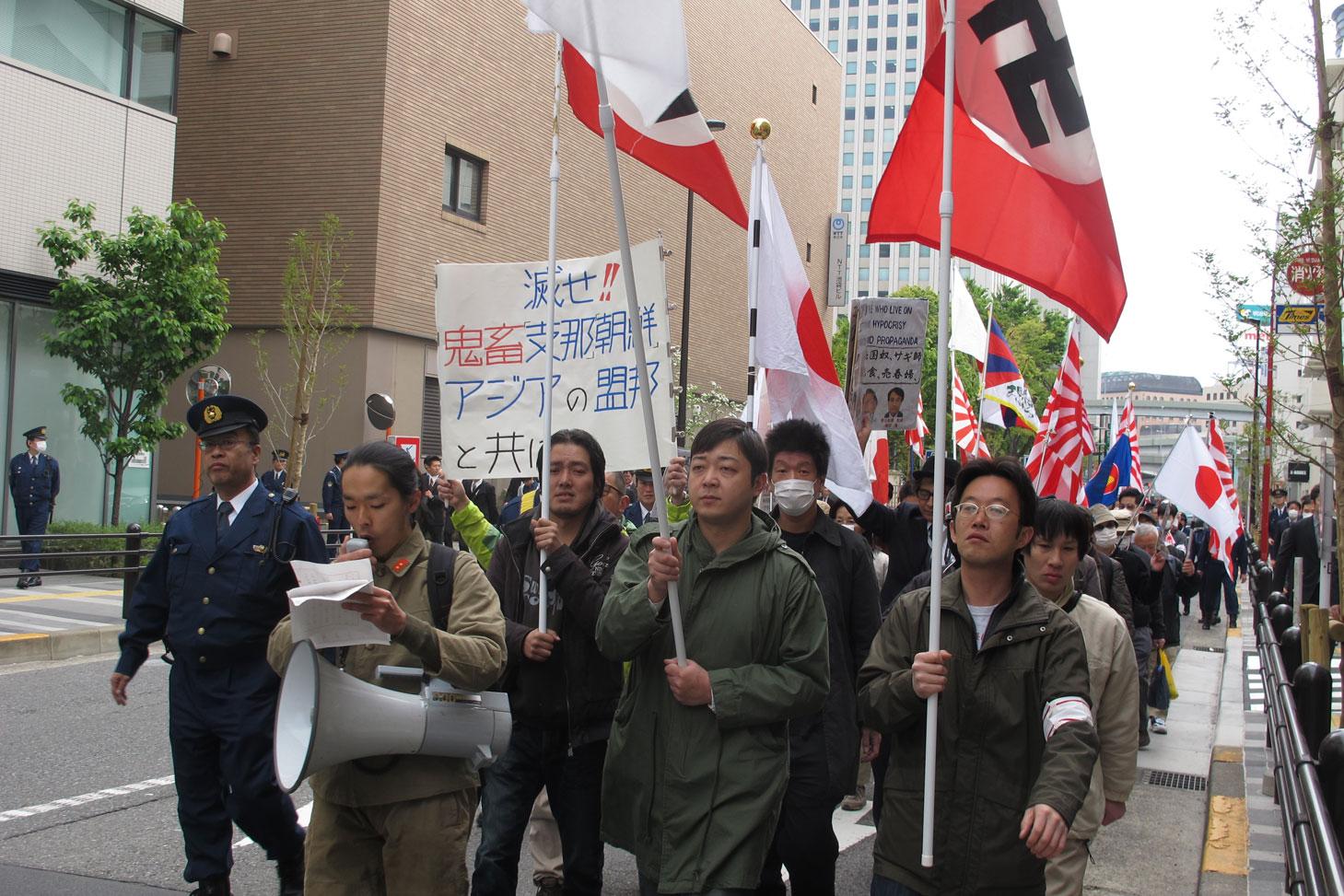 ハーケンクロイツの旗と日本の戦犯旗を持って東京 ...