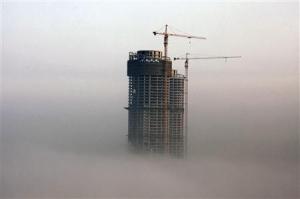2014-02-26_世界経済の不安要因に 中国の住宅バブル崩壊懸念01_26日、山東省日照市で霧の中に浮かび上がる建設中のビル。中国では不動産価格のバブル崩壊の懸念が広がる(ロイター)