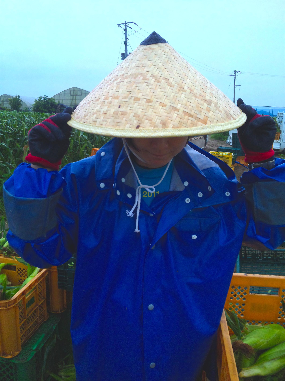 雨の日に竹笠で農作業