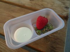 [写真]いちご狩り用の練乳&ヘタ入れカップ(左側に練乳、右側に摘んだイチゴとヘタが入っている様子)